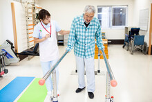 高齢男性の昇降訓練を手伝う女性ヘルパー