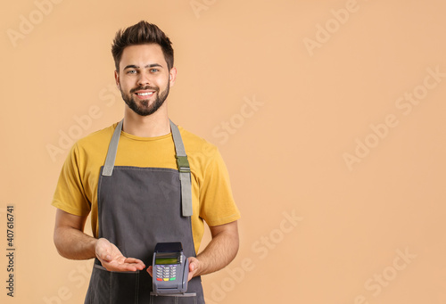 Fotografia Young waiter with payment terminal on color background