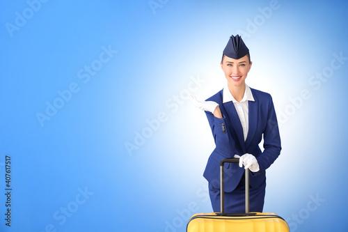 Fototapeta Beautiful stewardess with suitcase on color background