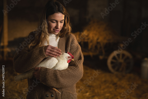 Fotografia Cinematic shot of young happy female farmer is caressing with love and care ecologically grown white hen for biological genuine food products industry in hay barn of countryside agricultural farm