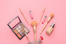 Shopping Cart With Makeup Brushes And Cosmetics On Color Background