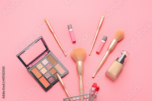 Fotografía Shopping cart with makeup brushes and cosmetics on color background
