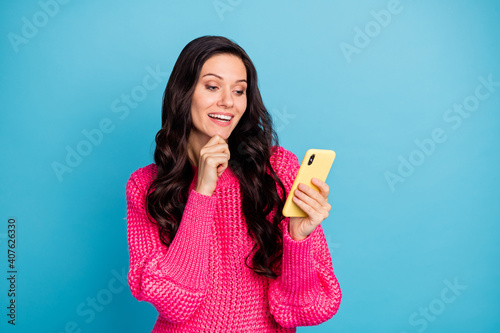Photo of smart minded happy woman hold hand chin smartphone think post isolated on blue color background