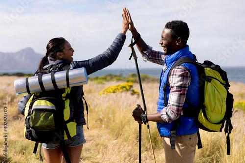 Fototapeta Fit african american couple wearing backpacks high fiving nordic walking on coas