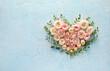 Leinwandbild Motiv Heart made of beautiful flowers on color background