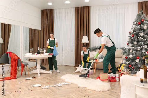 Obraz na plátně Cleaning service team working in messy room after New Year party