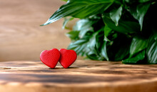 Valentine's Day Greeting Card With Two Red Hearts On A Wooden Rustic Background And Green Foliage Background. Concept Valentine's Day, Healthcare, Wedding, Family Happiness, World Heart Day, Love.