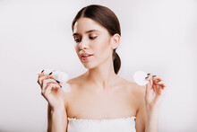 Young Brunette Woman In White Top Is Looking At Moisturizing Face Cream. Portrait Of Model Posing On Isolated Background