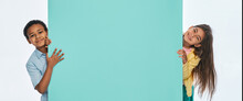 Multi-ethnic Children Peeking From Behind An Empty Turquoise Wall. Empty Space For Text With Kids