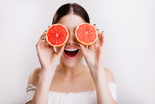 Happy Girl With Positive Emotional Facial Expression Covers Her Eyes With Oranges, Posing On Isolated Background