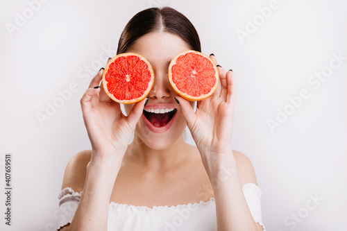 Fototapeta Happy girl with positive emotional facial expression covers her eyes with orange