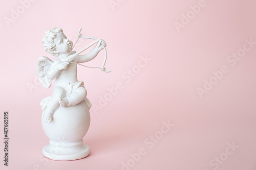 Cuadros en Lienzo figurine of an angel Cupid with a bow on a pink background