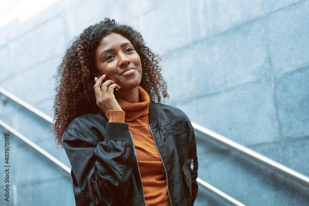 Fototapeta Afro american woman talking on cellphone in the city