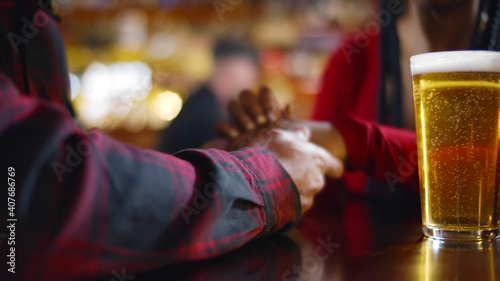 Canvas Close up of couple holding hands having beer sitting in bar
