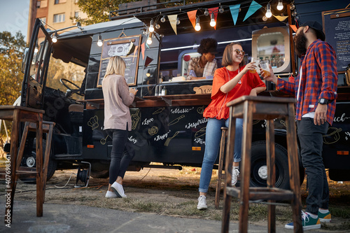 group of people enjoying in front of modified truck for mobile fast food service