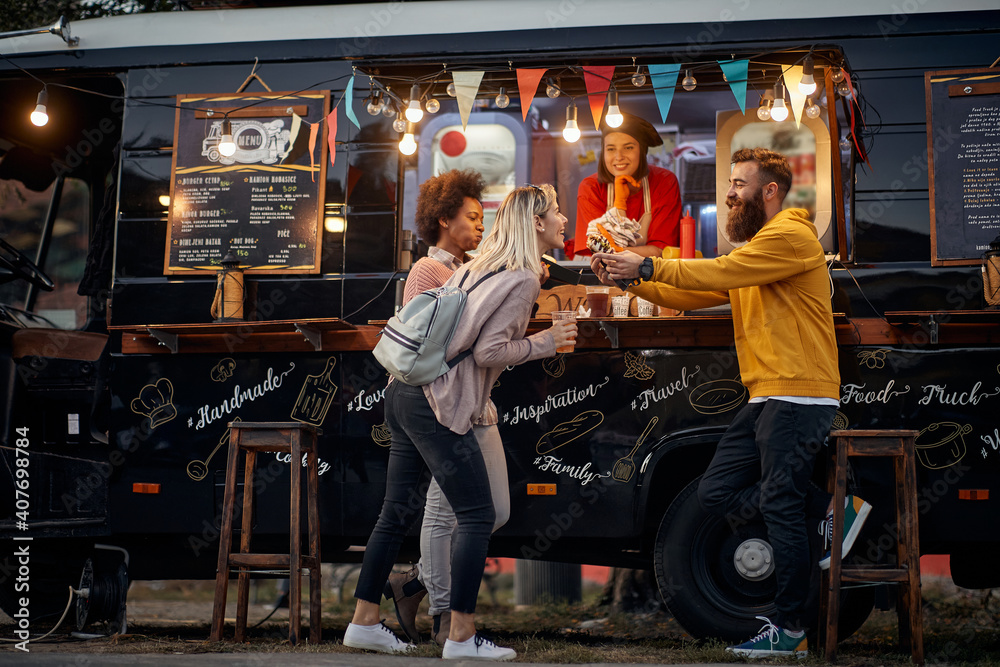 Fototapeta multiethnic young people having fun while eating in front of modified truck for mobile fast food service