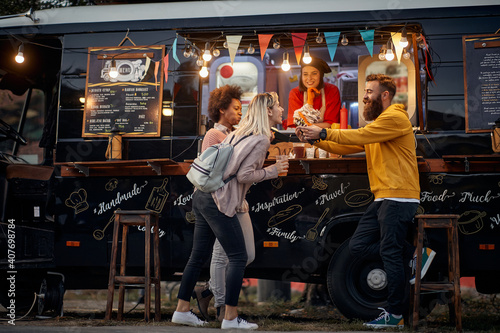 Fotografie, Obraz multiethnic young people having fun while eating in front of modified truck for