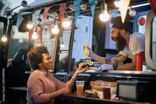 Cuadros en Lienzo young beardy caucasian employee in fast food laughing, adding a  mustard in a sa
