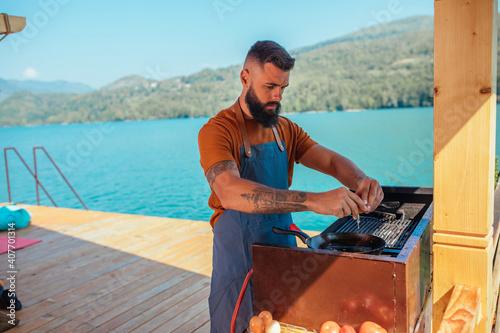 Obraz Male preparing breakfast in beautiful environment - fototapety do salonu