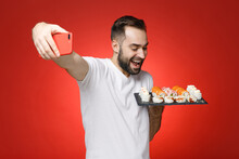 Excited Young Bearded Man 20s In White T-shirt Doing Selfie Shot On Mobile Phone Hold Makizushi Sushi Roll Served On Black Plate Traditional Japanese Food Isolated On Red Background Studio Portrait.