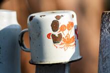 Old Enamel Mug On The Fence