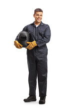 Full Length Portrait Of A Welder In A Uniform Holding A Protective Helmet And Smiling At Camera