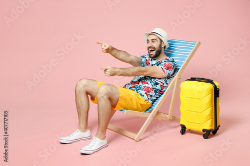 Fototapeta Full length excited young traveler tourist man in summer clothes hat sit on deck chair point index fingers aside isolated on pink background. Passenger travel on weekend. Air flight journey concept. obraz na płótnie