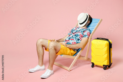 Full length of young traveler tourist man in summer clothes sit on deck chair covering face with hat isolated on pink background Poster Mural XXL
