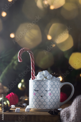 Fototapeta a white mug with a face painted on it full of marshmallow tea and a Christmas candy stick obraz