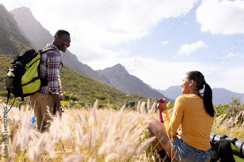 Fit african american couple wearing backpacks resting and drinking water in mountain countryside
