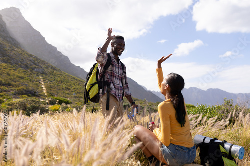 Fit african american couple wearing backpacks high fiving resting and drinking water in mountain cou