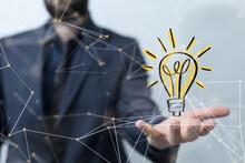 Holding Illuminated Light Bulb, Idea, Innovation And Inspiration Concept.