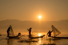INTHA FISHERMEN, INLE LAKE, SHAN STATE, MYANMAR - 18 January 2020: Three Traditional Fishermen Using Traditional Conical Net Technique Silhouetted At Sunrise.