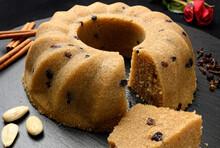 Homemade Semolina Halva With Raisins Served On Black Dish With Nuts And Cinnamon