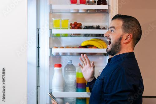 Fotografie, Obraz Surprised man looking inside the fridge