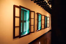 Hall With Many Windows And Green Venetian Blinds Closed Where Hash Sunlight Come Trough