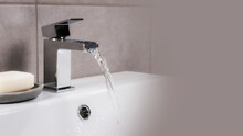 Closeup Shot Of Water Flowing From A Basin Mixer Tap In The Bathroom