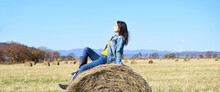 Young Brunette Woman Sitting On Top Of Haystack In Field. She Squinting From The Sun