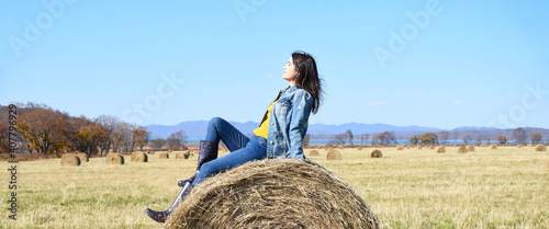 Fotografie, Tablou Young brunette woman sitting on top of haystack in field