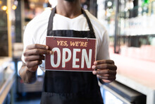 Portrait Of African American Male Barista Holding A Were Open Card