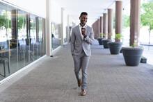 African American Male Businessman Walking Wearing Face Mask Talking On Smartphone