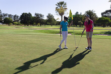 Two Caucasian Women Playing Golf One Taking Flag Out Of The Hole