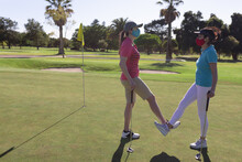 Two Caucasian Women Wearing Face Masks Greeting On Golf Course By Touching Ankles