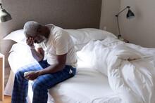 Senior African American Man Feeling Weak Sitting On Bed