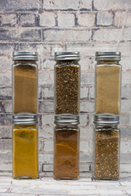 Vertical Shot Of Glass Spice Jars With Different Powders