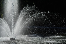 Close-up On The Water Jet Of A Round Fountain In A Park In Brussels. It Falls Back In Large Drops, Lit By A Summer Sun. Dark Background. Summer In The Capital, Belgium