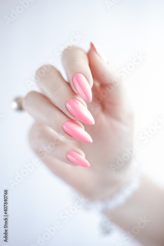 Obraz na plátne Female hand with long nails and a bottle of bright pink neon nail polish