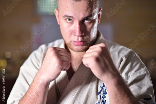 Obraz na plátně Sweaty and tired sportsman karate fighter stands in a fighting stance and looks