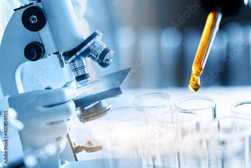 Obraz Microscope with laboratory glassware, science research and development concept, dropping chemical liquid to teat tube in lab. - fototapety do salonu