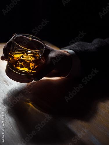 Man's hand holding a glass of whisky Fototapeta
